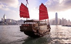 Boat with red sails on water near big city