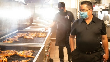 Masked men working on a restaurant grill