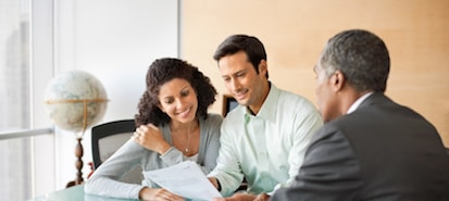 Couple Seated at a Table Reading a Report with their Financial Advisor