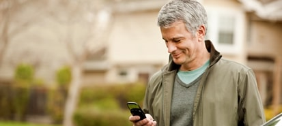 Man standing in driveway looking at mobile phone