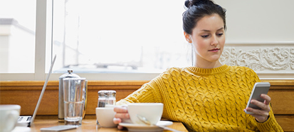 Young woman in café sitting and looking at phone
