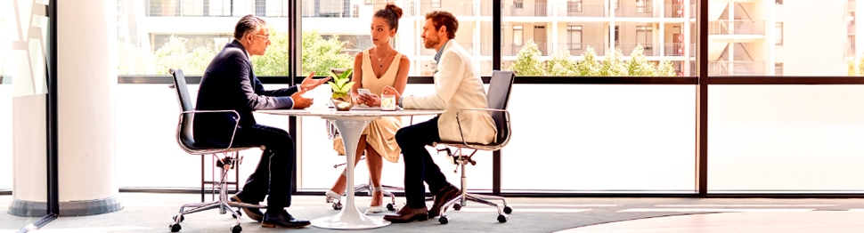 Three persons in discussion sitting at table