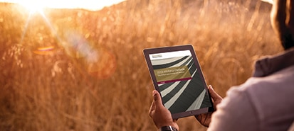 Person looking at tablet while sitting in a field