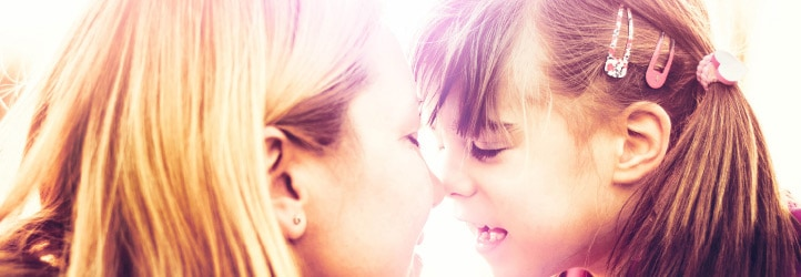 Woman touching noses with daughter