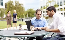 Two men outdoors with a laptop