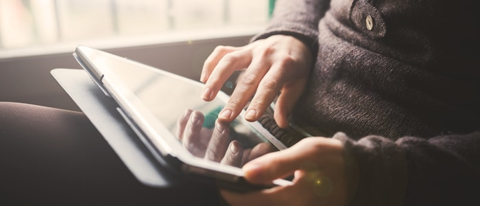 A person's hands and a tablet